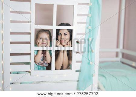 Happy Mother And Child Preparing For Sleep In Children House