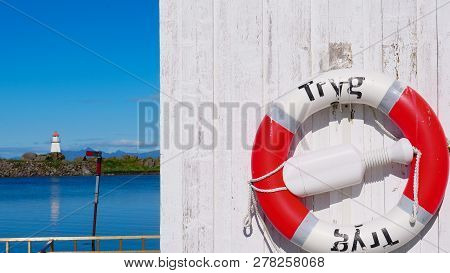 Rescue Ring In Norwegian Harbor And Seascape With Lighthouse At Hovsund Fishing Port, Gimsoya Lofote