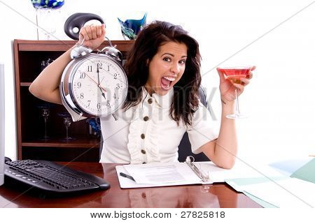 Young professional business woman working in a office holding up a giant clock and a martini at quiting time