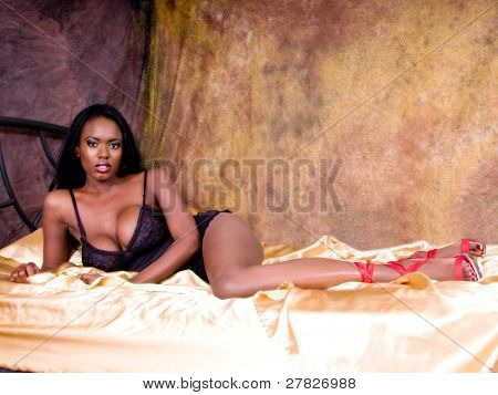 Sexy African American woman with very large breasts looking lovely in black lingerie  in a gold bedroom