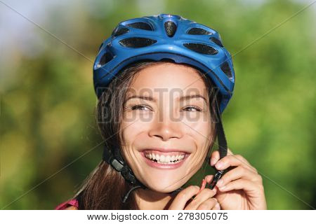 Asian woman wearing bike helmet for biking commute -city cyclist lifestyle. Safety on the road.