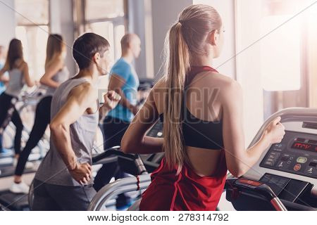 A Group Of Man And Girls Perform Exercises On A Treadmill. Group Jogging In The Gym All Together. Me