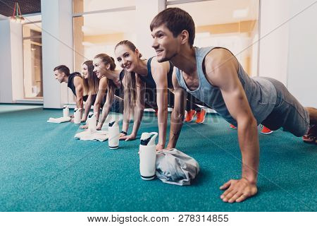 Group Men And Women Performs A Physical Exercise. A Happy Group Of People Performs An Exercise Bench