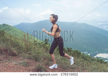 Fit Female Jogger Exercising, Running Uphill With Sea And Mountains In Background