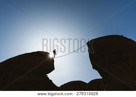 A Man Balancing Walking On Rope Over Precipice. Business, Risk Taking, Challenge,bravery, And Concen