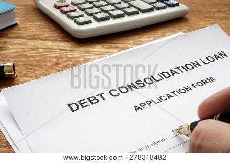 Man Filling In Debt Consolidation Loan Application.