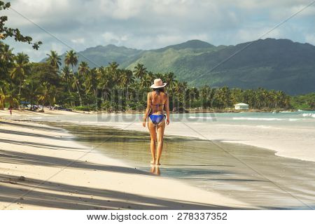 Traveler Girl Walking In Bikini On A Tropical Beach. Young Girl Traveler Walking In Nature. Traveler