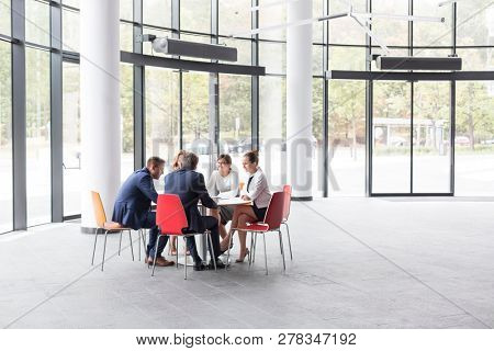 Business colleagues discussing while sitting at table during meeting in office lobby