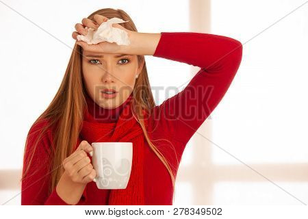 Young Ill Woman Drinks Tea As She Has Flu