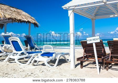 Sun Lounger Near Straw Umbrella Bed With Sign For Rent On The Sandy Beach By The Sea And Sky. Vacati