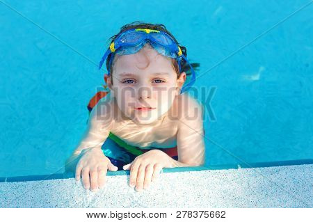 Little Preschool Kid Boy Making Swim Competition Sport. Kid With Swimming Goggles Reaching Edge Of T
