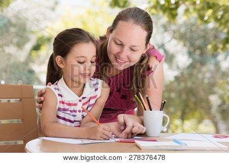 Happy Smiling Mother And Child Daughter Having Fun And Drawing Pictures Outdoors In Garden In Summer