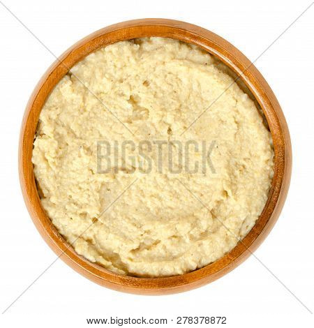 Hummus In Wooden Bowl. Levantine Dip Or Spread Made From Cooked, Mashed Chickpeas, Blended With Tahi