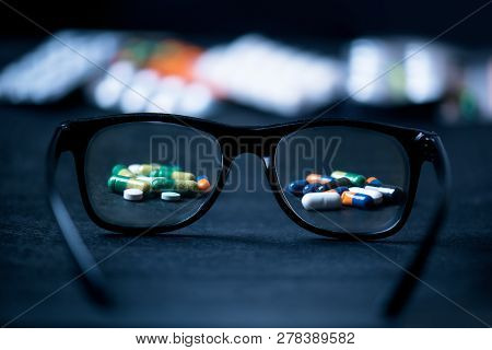 Pills, Tablets Focused In Glasses On A Black Background. Pharmacy And Medicine Concept. Focused On A