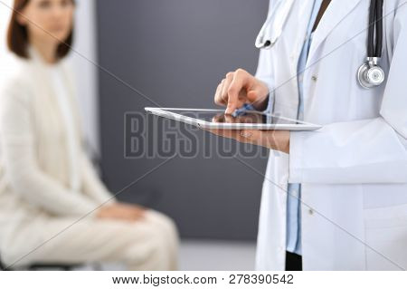 Female Doctor Woman Using Digital Tablet While Standing Near Reception Desk At Clinic Or Emergency H
