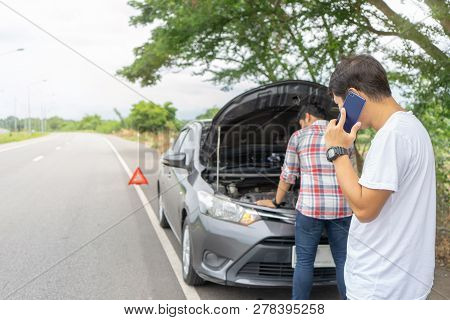 Friends Fixing Car Broken Down On Highway  Calling For Help On Mobile Phone. Two Man Friends Talking
