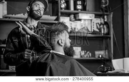 Hipster Bearded Client Getting Hairstyle. Barber On Cheerful Face With Hairdryer Styling Hair Of Cli