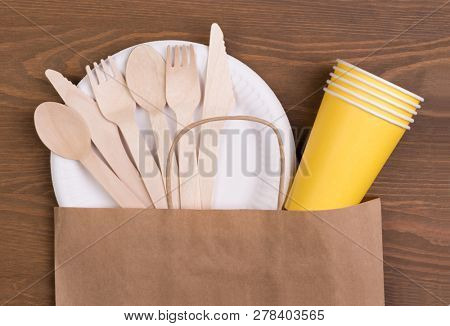 Disposable paper plates and cups and wooden cutlery on wooden table in a paper bag