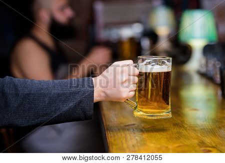 Beer Mug On Bar Counter Defocused Background. Glass With Fresh Lager Draft Beer With Foam. Male Hand