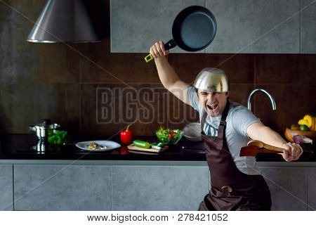 Funny Loser Man Male Guy With Metal Sieve, Frying Pan, Wooden Kitchen Utensils And Apron Trying To C