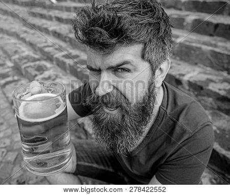 Guy having rest with cold draught beer. Hipster on cheerful face drinking beer outdoor, raising drink up. Cheers concept. Man with beard and mustache holds glass with beer while sits on stone stairs poster