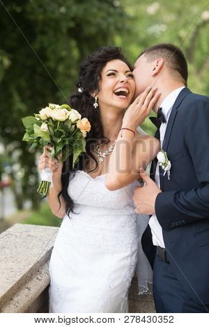 Woman And Man Smile On Wedding Day. Groom Kiss Happy Bride With Bouquet. Wedding Couple In Love. New