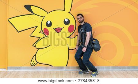 Tokyo, Japan - August 2018: Happy Tourist With A Pokemon Pikachu Figure At Pokemon Center Store In S