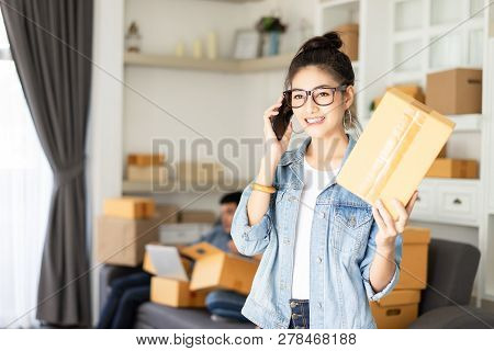 Young Asian Woman Talking With Customer On Mobile Phone At  Home Office With Partner At The Backgrou