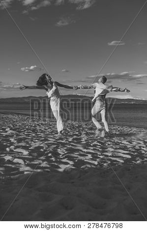 Man And Woman Dancing, Couple Happy On Vacation. Couple In Love Running On Beach, Seashore. Couple I