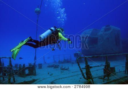 Diver Exploring The  Sunken Wreck Of A Russian Gunship
