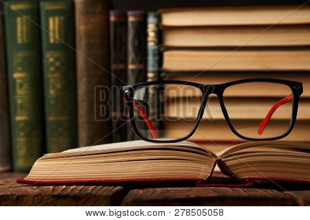 Old Books And Reading Glasses On Desk In Library Room