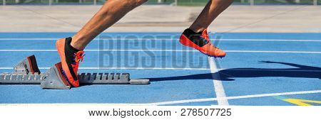 Track spikes shoes feet on starting blocks on running track and field stadium blue lanes. Sprinting man athlete runner at run start leaving at the beginning of the race competition. Banner crop.