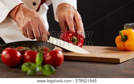 Male Chef Cutting Fresh Capsicum Or Peppers
