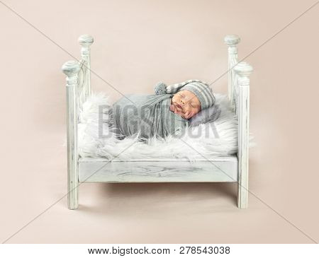 Cute little baby in hat sweetly sleeping in white bed covered with gray blanket