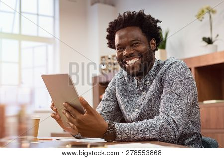 Happy casual african man using digital tablet at office. Portrait of smiling black businessman sitting on chair using tablet pc. African american casual business man looking at camera.