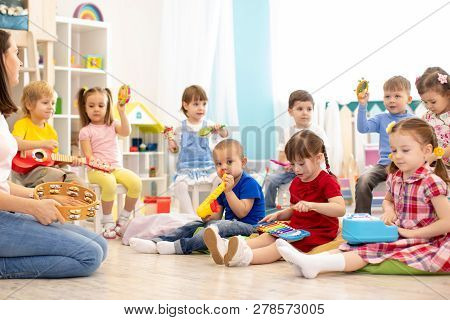 Kindergarten Children Playing Different Musical Toys. Early Musical Education In Day Care Centre