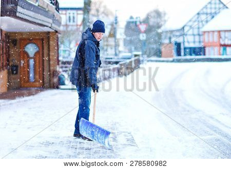 Man With Snow Shovel Cleans Sidewalks In Winter During Snowfall. Winter Time In Europe. Young Man In