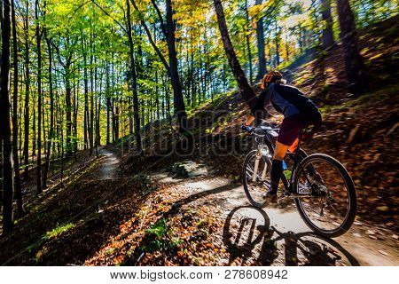 Cycling woman riding on bike in spring summer mountains forest landscape. Woman cycling MTB flow trail track. Outdoor sport activity.