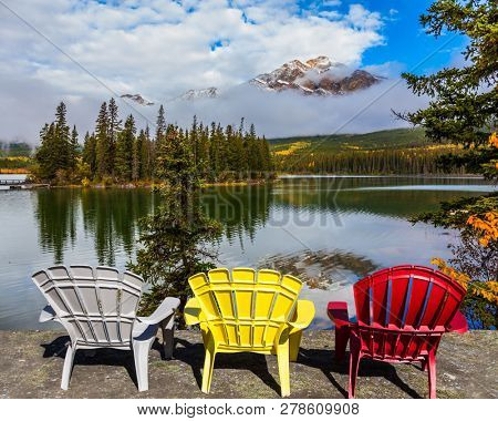 Three comfortable multi-colored deck chairs stand by the Piramid lake. Rocky Mountains of Canada. Concept of ecological, active and photo-tourism