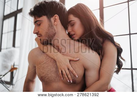 Satisifed And Passionate Couple Sitting On Bed In Room Together. She Ambrace Him Behind. They Hold H