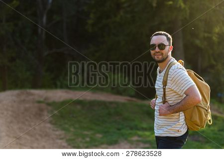 Hiking Man Portrait With Backpack Walking In Nature. Caucasian Man Smiling Happy With Forest In Back
