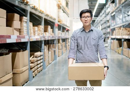 Young Asian Man Carrying Cardboard Box Between Row Of Shelves In Warehouse. Shopping Warehousing Or