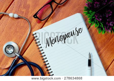Top view of stethoscope,pink eyeglasses,plant,pen and notebook written with Menopause on wooden background.Health concept. poster