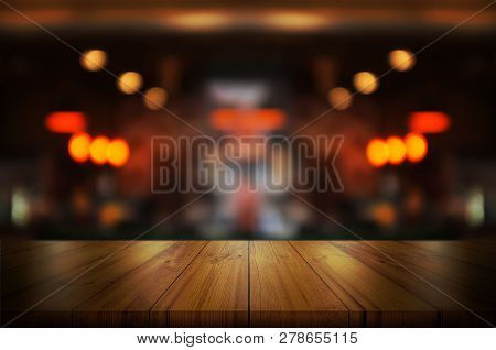 Empty Wooden Table Top With Blurred Coffee Shop Or Restaurant Interior Background. Abstract Backgrou