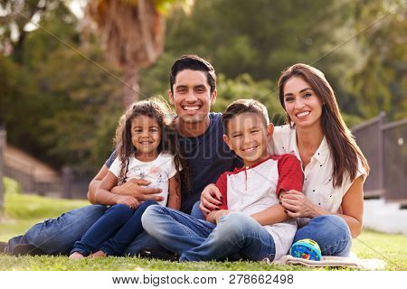 Happy young Hispanic family sitting the on grass in the park smiling to camera, close up