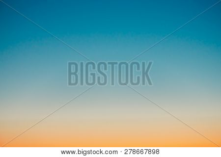 Predawn Clear Sky With Orange Horizon And Blue Atmosphere. Smooth Orange Blue Gradient Of Dawn Sky.