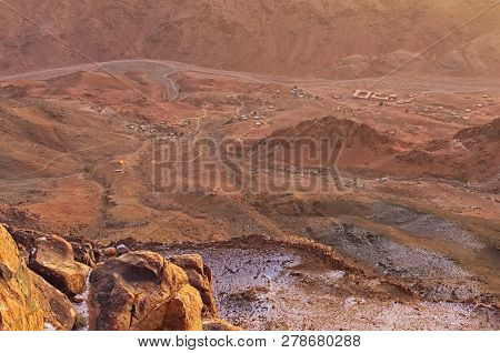 Pilgrimage place and famous touristic destination. Aerial view of small village at the foot of Mount Sinai (Mount Horeb, Gabal Musa, Moses Mount) during sunrise. Sinai Peninsula of Egypt. poster