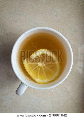 Top View On White Porcelain Cup Of Tea With Lemon Slice