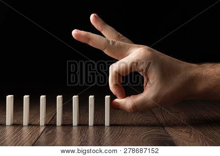 Creative Background, Male Hand Pushing White Dominoes, On A Brown Wooden Background. Concept Of Domi