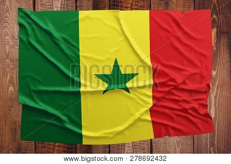 Flag of Senegal on a wooden table background. Wrinkled Senegalese flag top view. poster